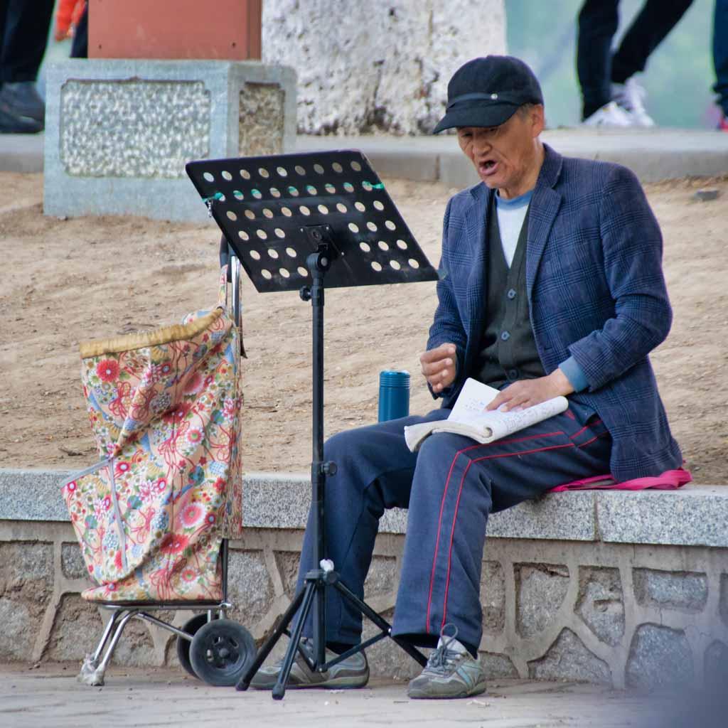 Ein alter Herr mit Mütze singt aus vollem Hals am Ufer des Sees im Yuyuantan-Park