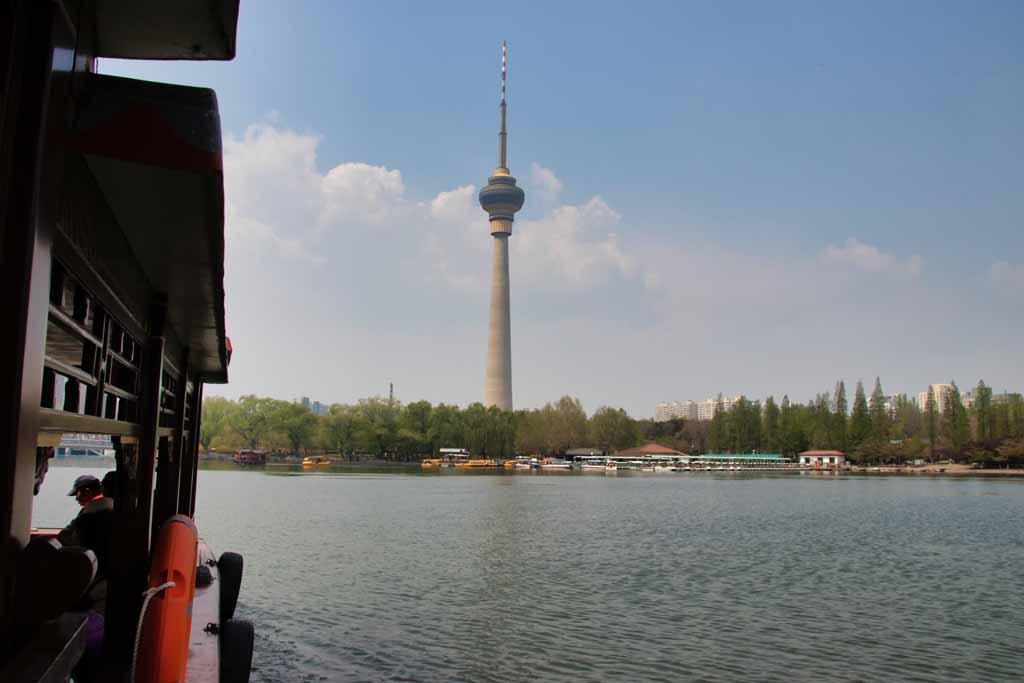 Fahrt mit dem Pendelboot über den See im Pekinger Yuyuantan-Park mit Blick auf den Fernsehturm.