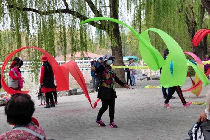 Dancing Ayis mit bunten Bändern im Yuyuantan-Park in Peking