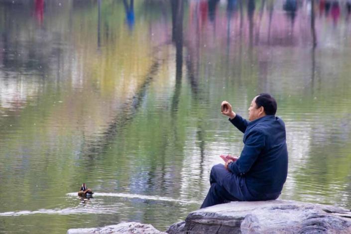 Ein Mann sitzt am See im Yuyuantan-Park in Peking