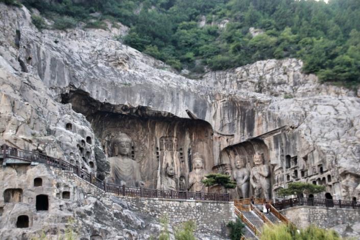 Blick vom Fluss aus auf die großen Buddhas der Longmen-Grotten