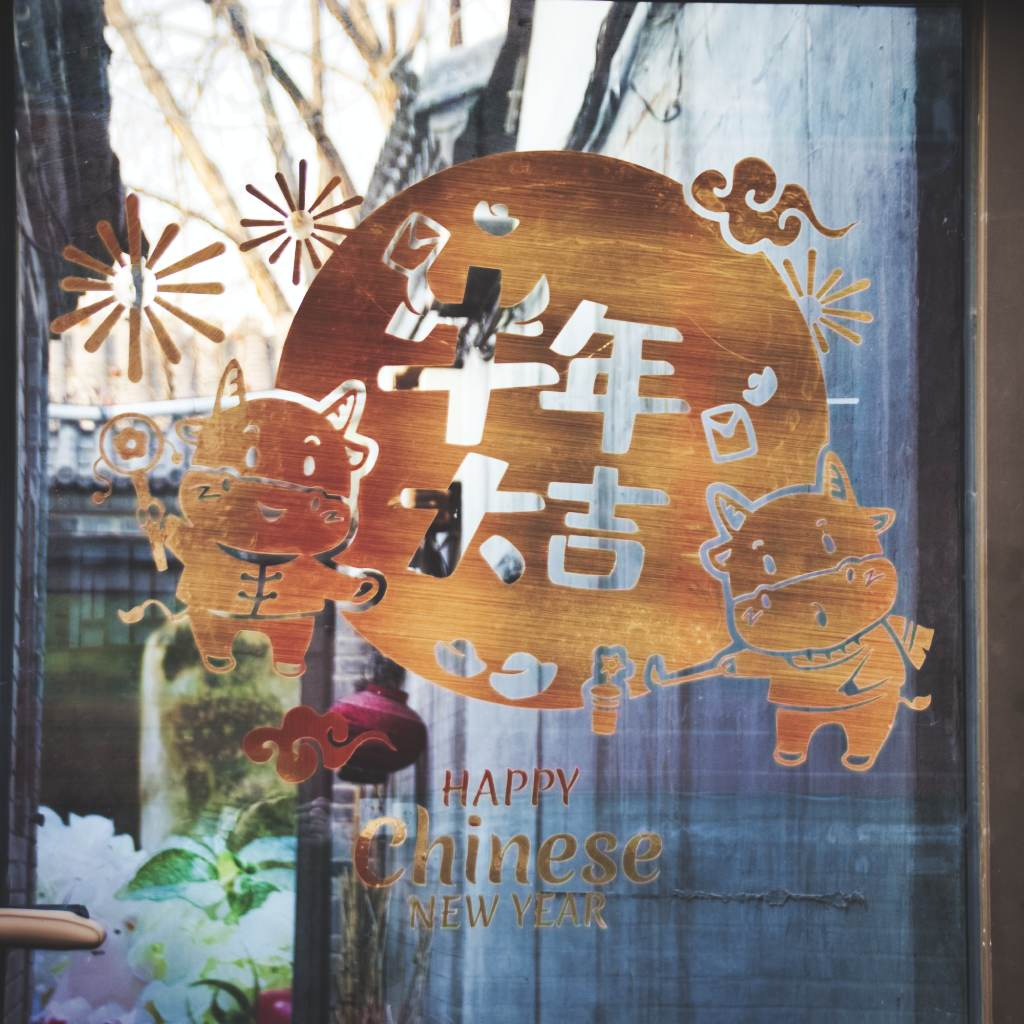 Goldene Neujahrsdeko an der Glastür eines Geschäfts im Pekinger Wudaoying-Hutong