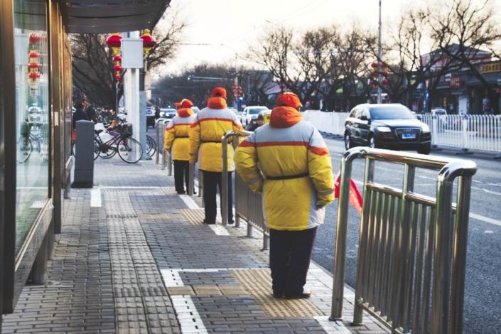 Bushaltestelle mit Helfern in gelben Jacken in der Andingmen Inner Street in Peking