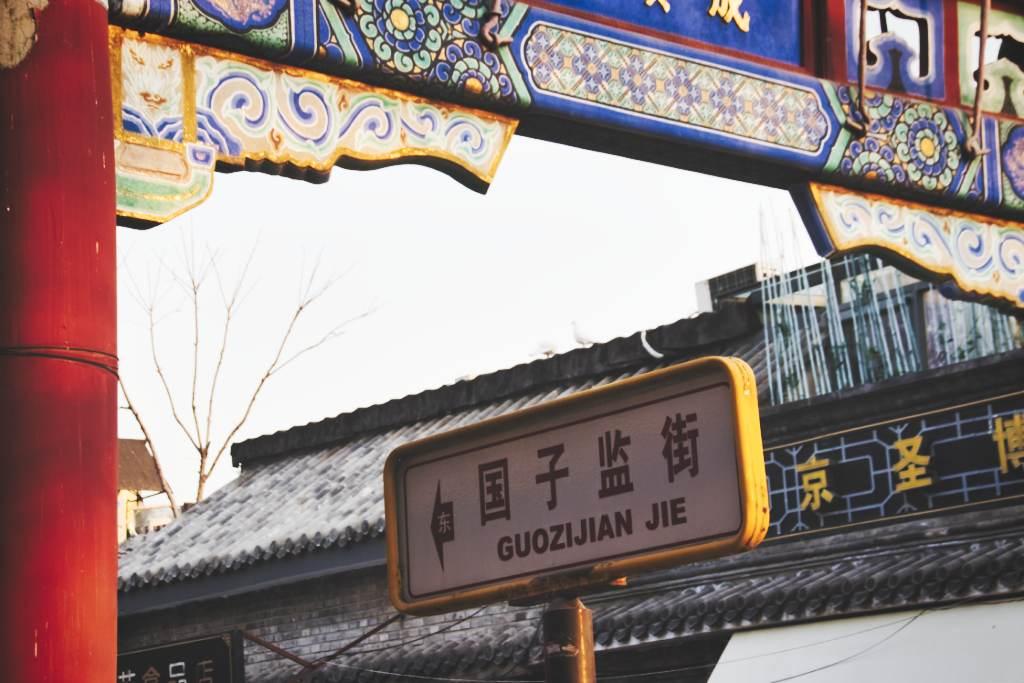 Straßenschild: Guozijian Jie in Peking, eingerahmt vom Torbogen