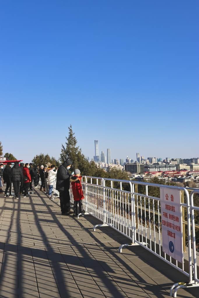 Plattform vor dem Wanchun-Pavillon im Jingshan-Park, nur wenige Besucher genießen blauen Himmel und Blick auf den CBD