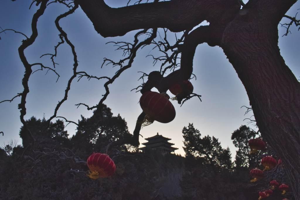 Gegenlicht Aufnahme: Pavillon auf dem Kohlehügel von unten durch die mit roten Laternen geschmückten Zweige eines Baums gesehen.