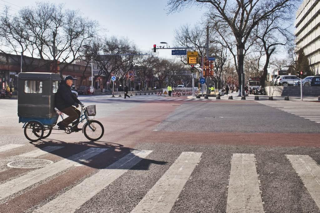 Ein alter Mann fährt mit einem Dreirad mit Fahrgastkabine über die Kreuzung vor der Ghost Street in Peking.