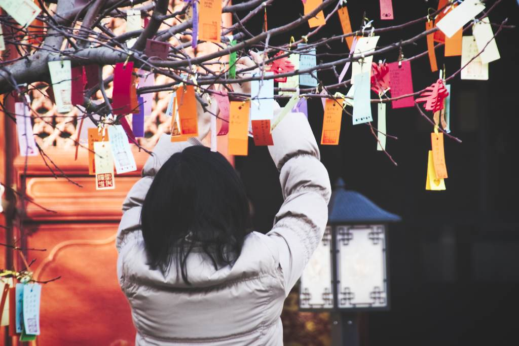 Eine Frau hängt Wunschkarten an einen Baum im Zhihua-Tempel