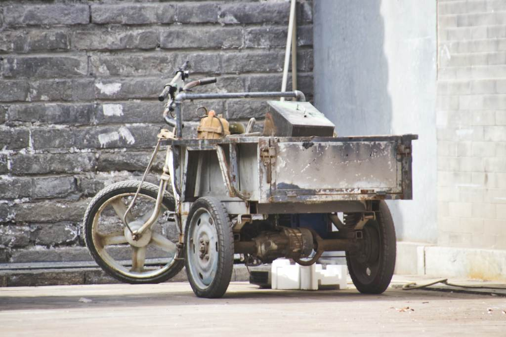 In die Jahre gekommenes Tuktuk vor dem Ausstellungsgebäude