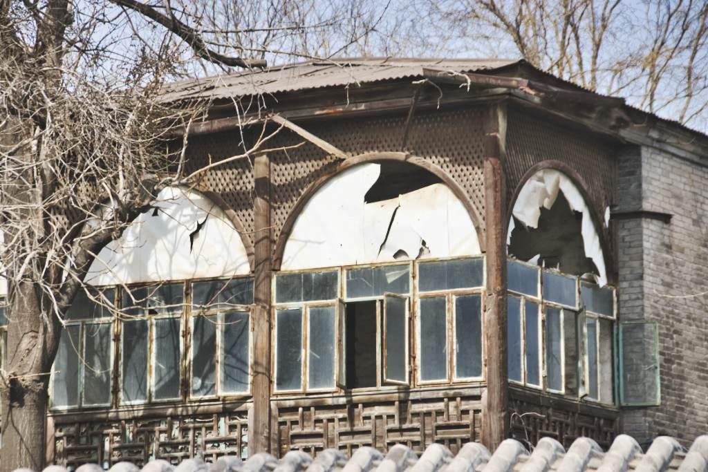 Vernachlässigtes Haus mit kaputten Scheiben am Houhai in Peking.