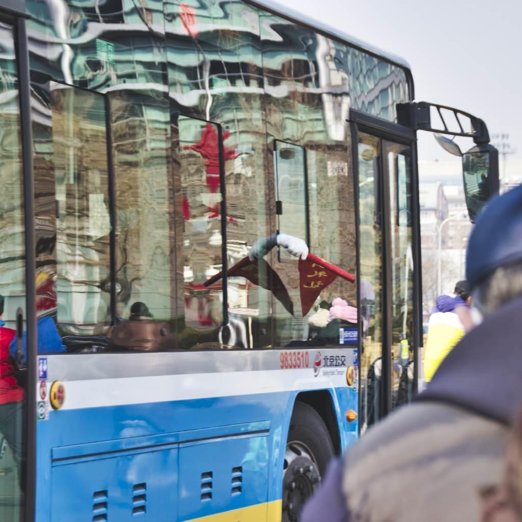 Abbiegender Bus in Peking mit roter Fahne, die aus dem Fenster heraus gewedelt wird