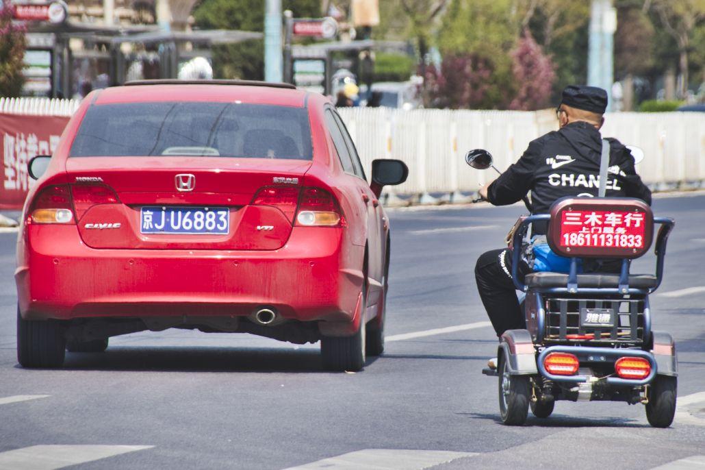 Roter PKW und älterer Mann auf Dreirad-Tuktuk, der Mann trägt ein schwarzes Sweatshirt mit dem Chanel-Schriftzug auf dem Rücken.