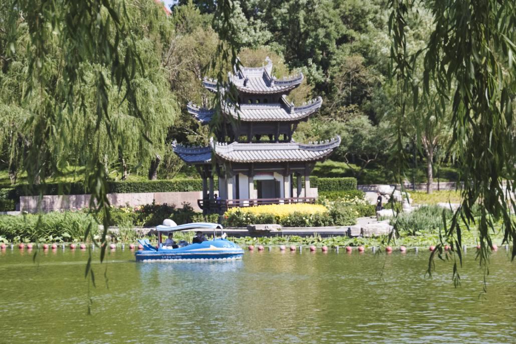 Chinesischer Pavillon am See mit blauem Elektroboot davor