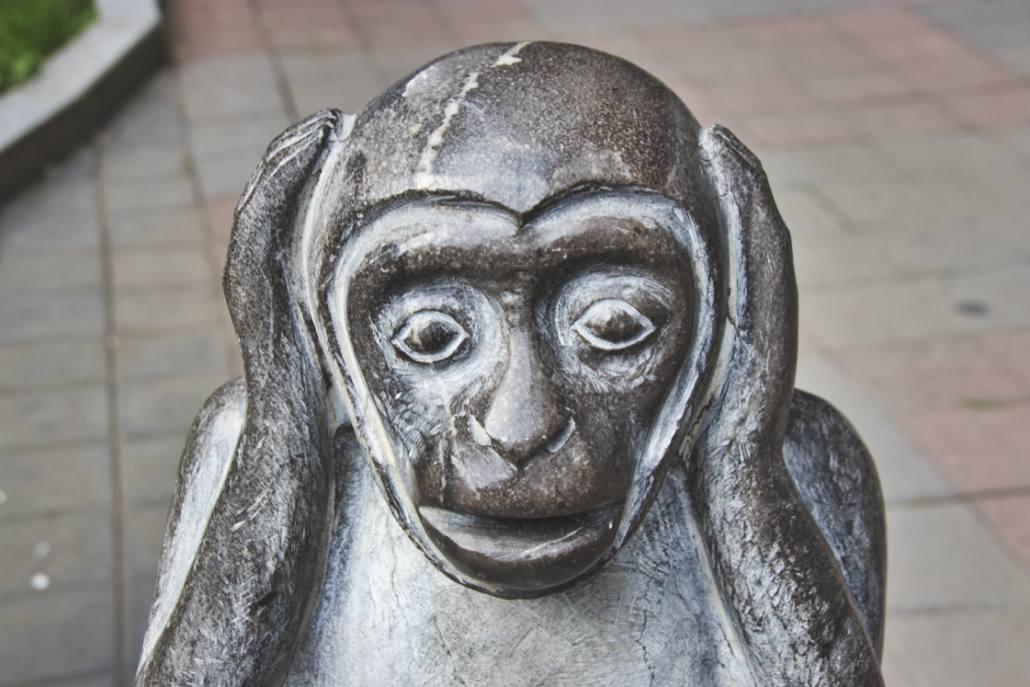 Affenstatue mit Händen über den Ohren, konsterniertem Gesichtsausdruck