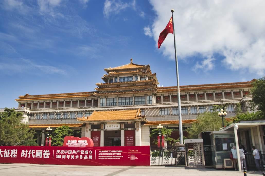 Da Gebäudes des National Art Museum in Beijing - mit wehender roter Fahne und dem Ausstellungsbanner am Zaun