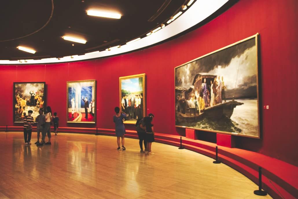 100 Jahre KP - Ausstellung im National Art Museum, vier große Gemälde an rot gestrichener, geschwungener Wand, davor zahlreiche Besucher.