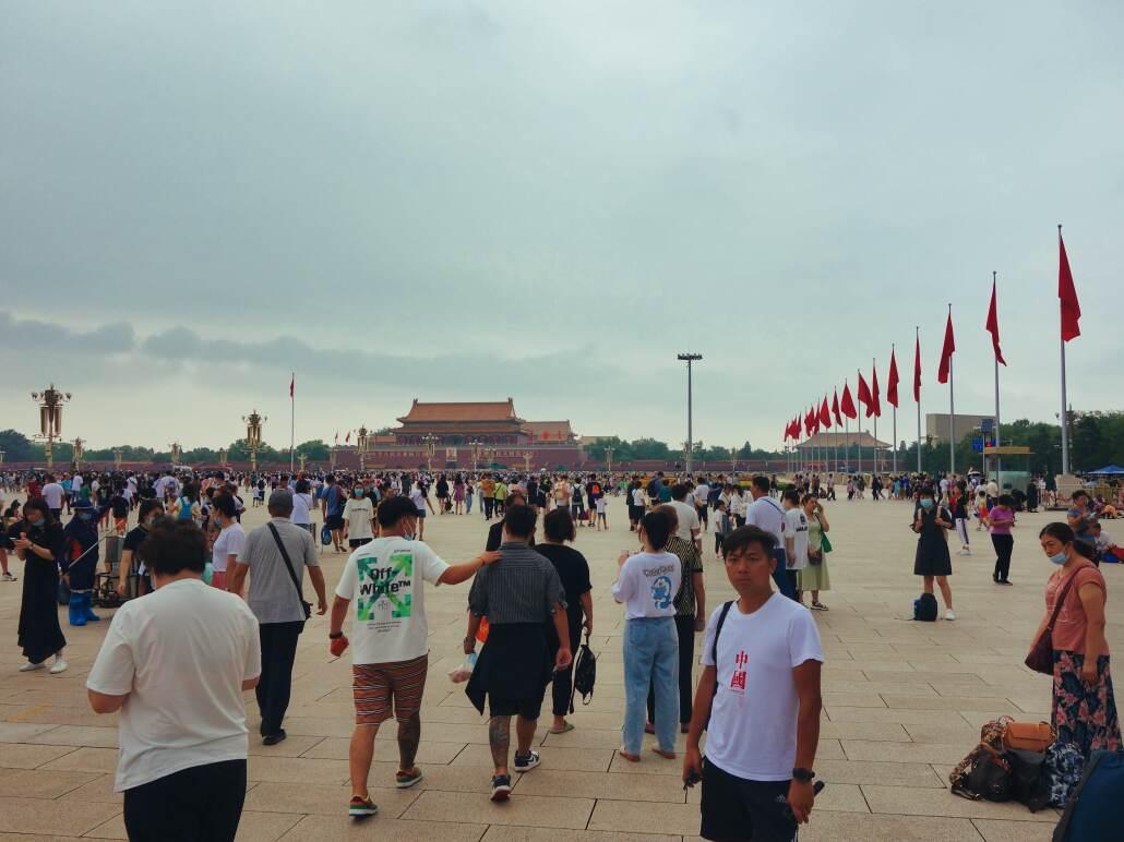 Spaziergänger, Touristen, Familien schlendern über den Tian'anmen oder sitzen auf dem Boden und warten. Im Hintergrund das Tor des Himmlischen Friedens.