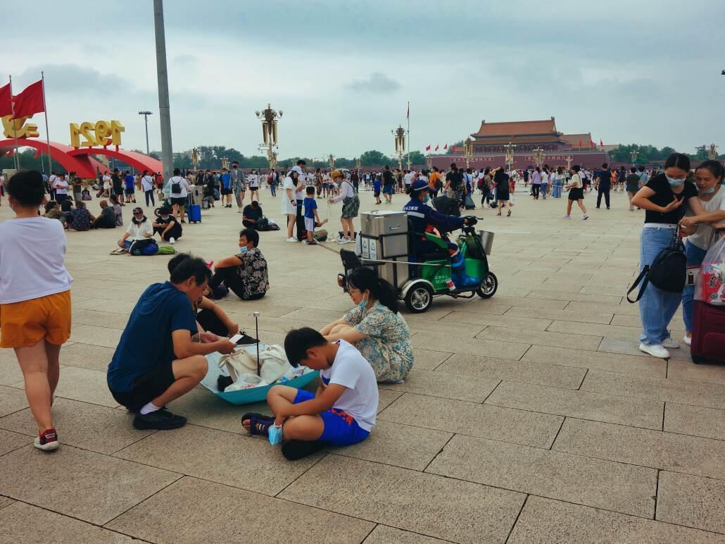 Spaziergänger, Touristen, Familien schlendern über den Tian'anmen oder sitzen auf dem Boden und warten, während ein kleines Reinigungsfahrzeug herumfährt. Im Hintergrund das Tor des Himmlischen Friedens.