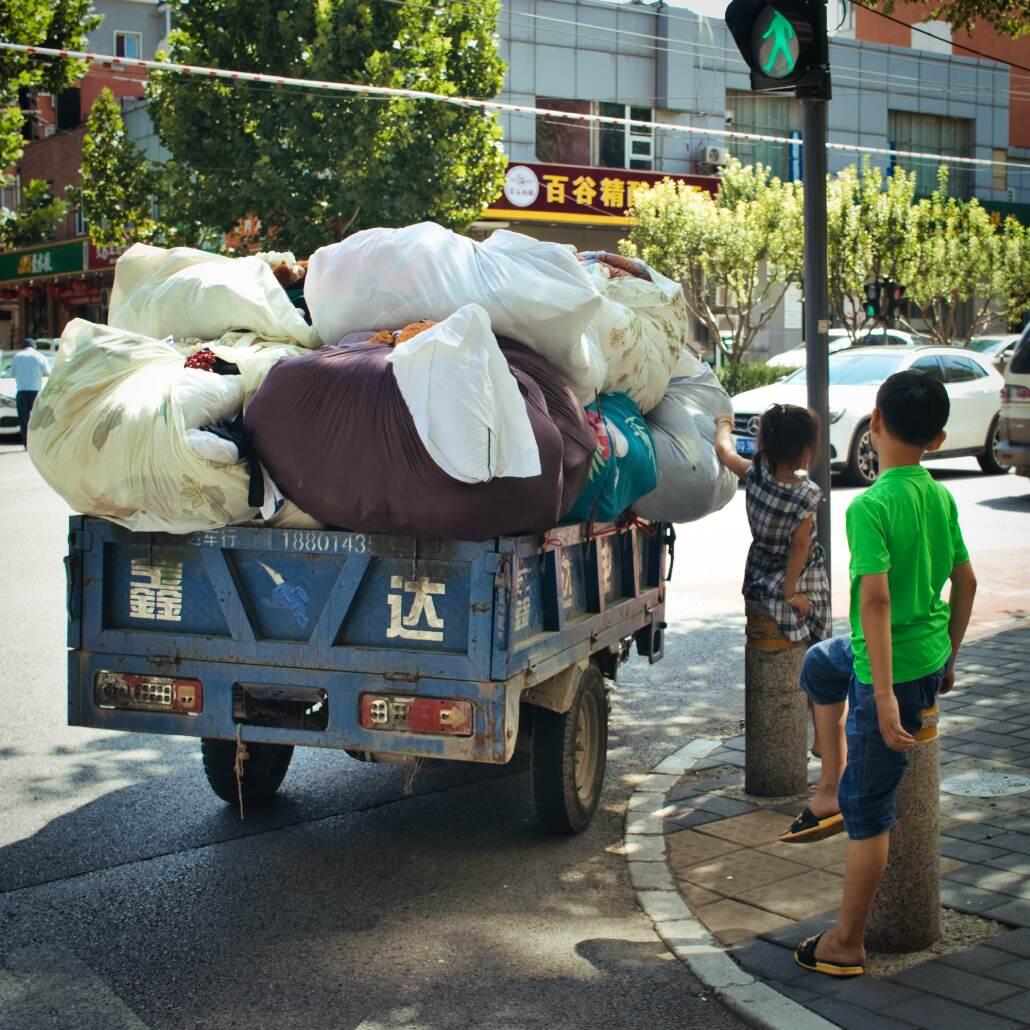 Zwei Kinder stehen einem mit Wäschesäcken voll beladenem Tuktuk.